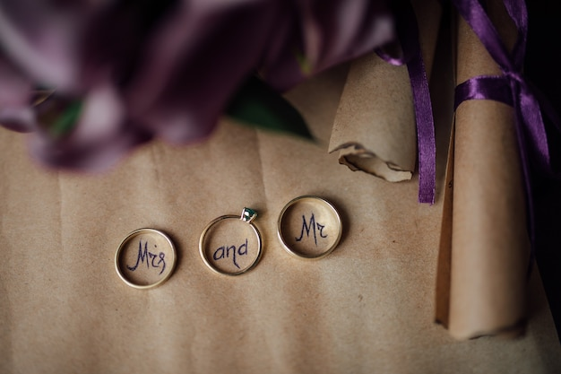 Wedding planning concept. gold rings with mr and mrs text inside on white background with fresh roses, free space.