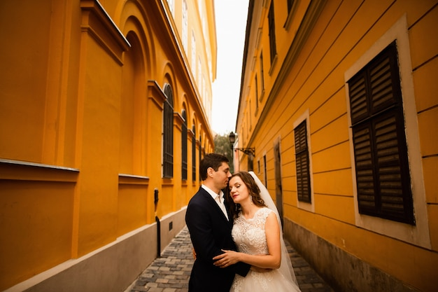 Wedding portrait of loving newlyweds in the old town.
