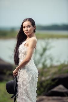 岩と森のデザイナーからのかわいい花嫁アジアの女性の白いゴージャスなウェディングドレスの結婚式の肖像画、ヴィンテージスタイル
