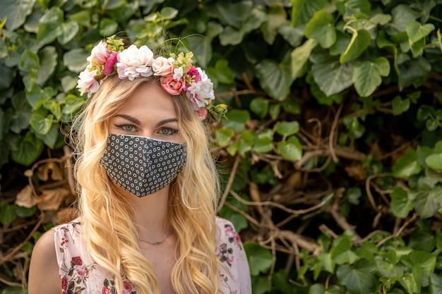 彼女の頭に花の花輪と彼女の口にマスクを持つドレスを着た女性の結婚式の肖像画。コロナウイルス流行時の対策