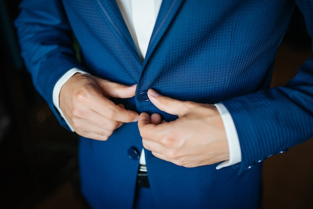 Wedding preparation. groom buttoning his blue jacket before wedding.