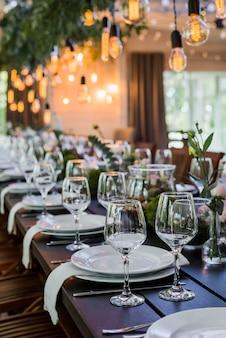 Свадебный прием с лампочками эдисона и декором из зелени.