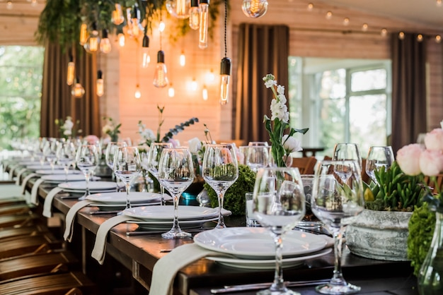Wedding reception table with edison bulbs and decor of greenery.