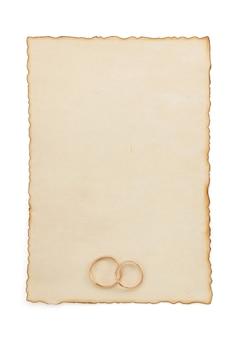 Обручальное кольцо и старая бумага, изолированные на белом фоне