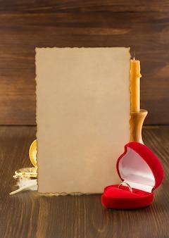 Обручальное кольцо и состаренная бумага на дереве