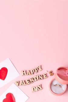 ピンクの背景に幸せなバレンタインデーの碑文と結婚指輪と多くの心