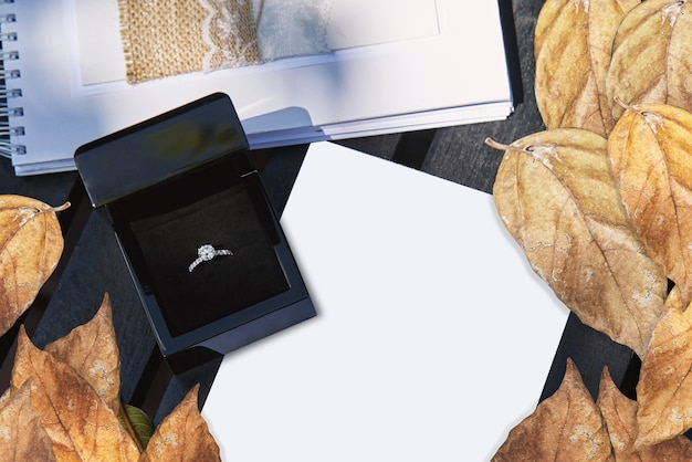 Wedding ring in black box on white blank paper with dry leafs decoration