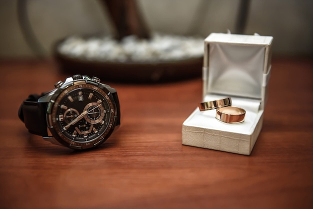 Wedding ring in a box and watch the groom on the table