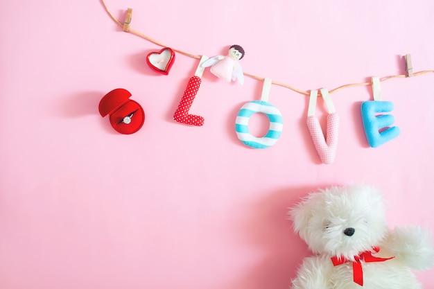 ウェディングリング、クラフト、ハンドピンクの背景に愛のアルファベットを作った