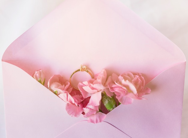 Wedding ring in envelope with pink flowers