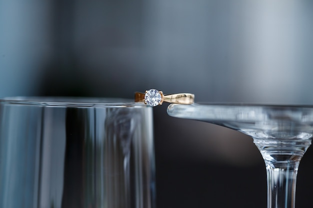 A wedding ring made of precious metal with a diamond stone lies in a glass