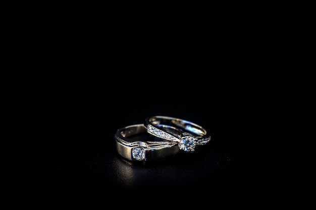 부드러운 푹신한와 배경 위에 빛이 검은 테이블에 결혼 반지