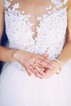 花嫁の指に結婚指輪。美しいマニキュア。