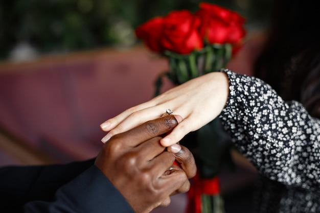 여자의 손가락에 결혼 반지. 빨간 장미 꽃다발입니다. 약혼 선물.