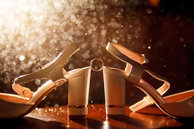 Wedding ring between the shoes of the bride. wedding golden rings between the bride's shining shoe.