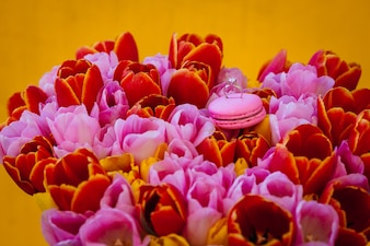 Wedding ring stands on pink macaroon on a bouquet of tulips
