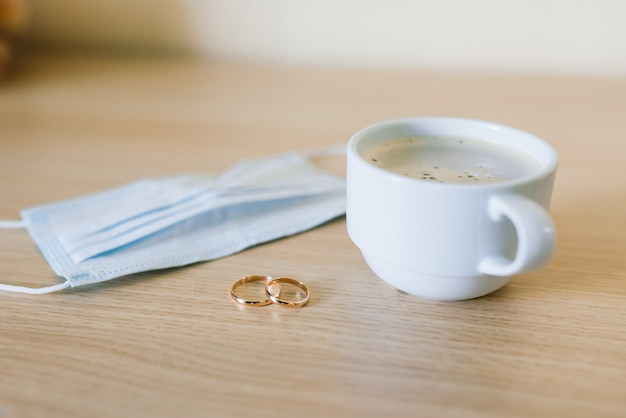 医療用フェイスマスク付き結婚指輪。コロナウイルスのパンデミック時の離婚と結婚の分離。