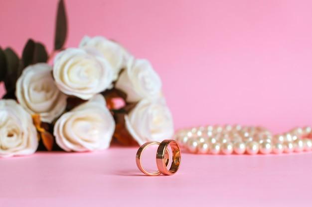 Обручальное кольцо с размытой белой розой и жемчужным ожерельем на фоне, изолированном на розовом