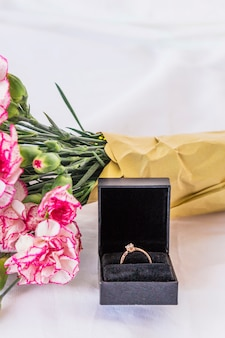 Wedding ring with flowers bouquet on table
