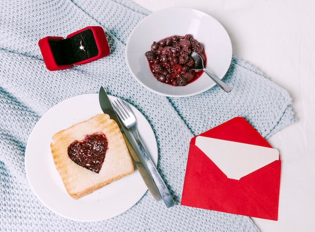 Wedding ring with toast with jam in heart shape on scarf