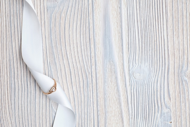 Wedding ring with a white ribbon on a wooden background. top view.