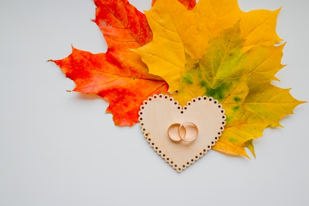 Wedding ring on wooden heart on autumn leaves background. golden wedding rings Premium Photo