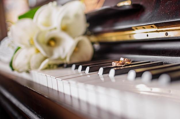 결혼 반지와 피아노 건반에 흰색 칼라스 꽃다발.
