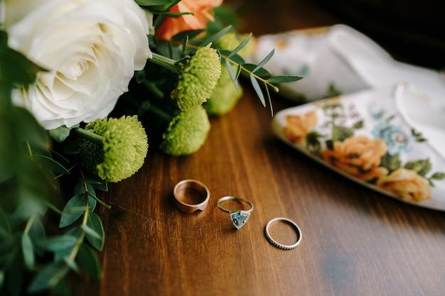 結婚指輪と女性の結婚式の靴と花の花束と木製のテーブルの婚約指輪