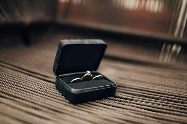 Обручальные кольца и помолвочное кольцо с крупным камнем в черной бархатной шкатулке
