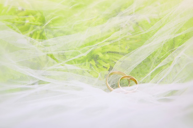 白いベールの上の結婚指輪と菊の花束