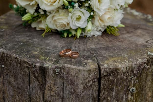 Обручальные кольца и букет невесты на пеньке, свадебный букет