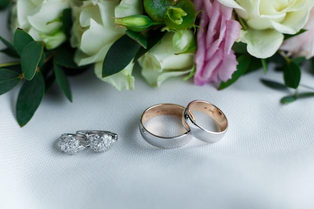 花と穏やかなヘアピンの近くにある結婚指輪とイヤリング