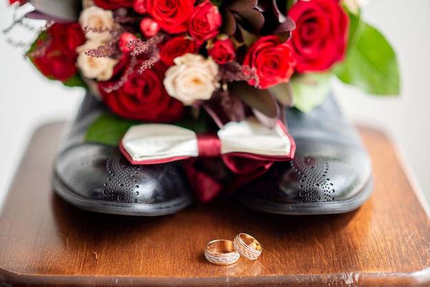 Обручальные кольца и свадебный букет из красных и розовых роз