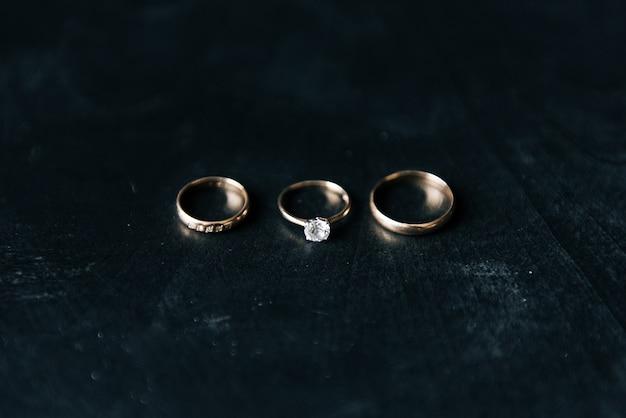 黒い木製のテーブルに配置された結婚指輪。ウェディングカード