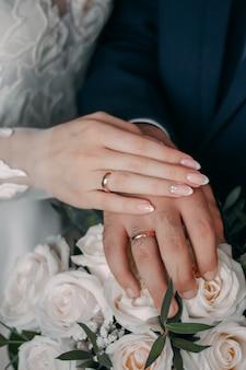 Обручальные кольца b w. руки жениха и невесты с кольцами.