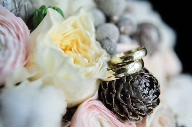 Wedding rings on the background of the bride bouquet