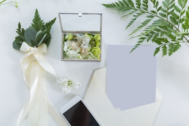 Wedding rings on a beautiful background with bridal accessories, top view flat lay