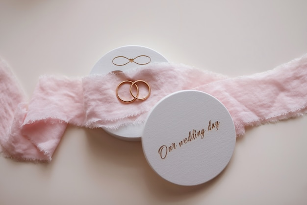 Wedding rings in a beautiful box lie on the table. pink ribbon. the infinity symbol