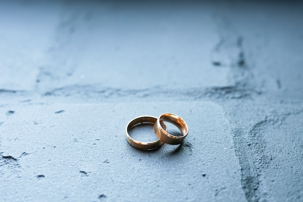 Wedding rings on blue brick. gold rings concept ol love and wedding