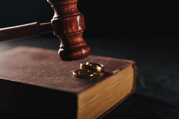 Wedding rings on book and judge gavel