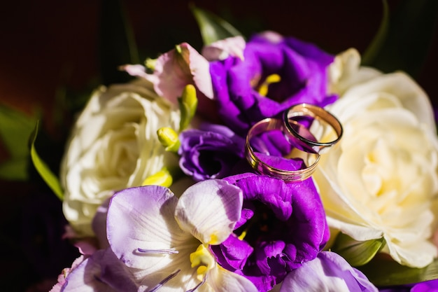 Wedding rings on a bouquet of white and blue flowers