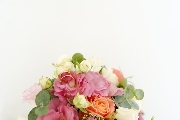 Wedding rings on the bouquet with flowers roses