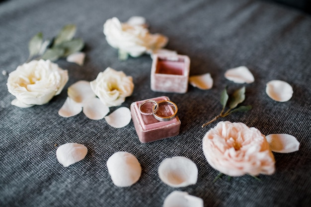 Wedding rings in a box on a of flowers