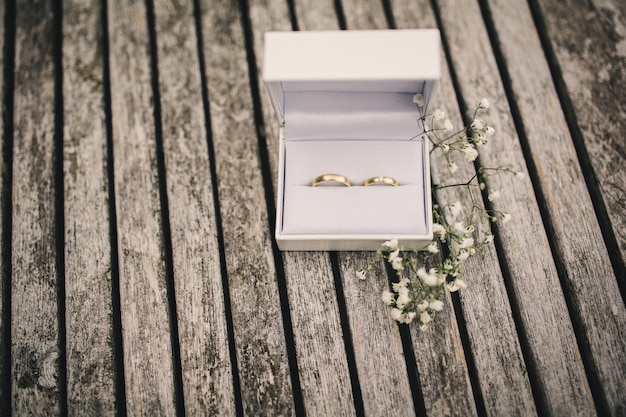 Wedding rings in a box on the table. small flowers on a wooden table