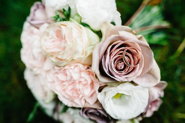 Обручальные кольца невесты и жениха, букет невесты с нежными пастельными цветами и розовыми розами и зеленью, лежащими на траве. осень. плоская планировка. вид сверху.