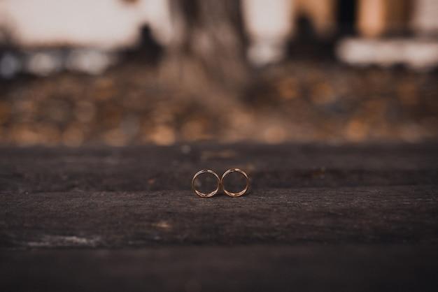 Обручальные кольца жениха и невесты на деревянных фоне