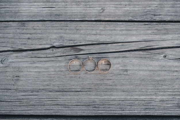 木製の背景に結婚指輪の新郎新婦