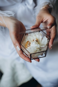 Wedding rings of the bride and groom are in a glass box on the succulent, the box is on the bride's hands.