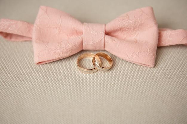 Wedding rings of bride and groom near pink groom's bow tie