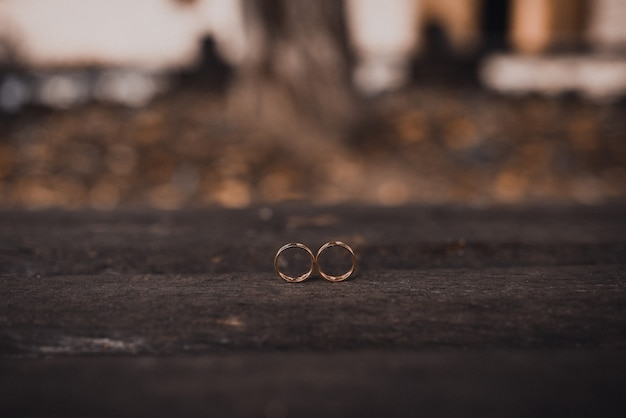 Wedding rings bride and groom on the wooden background
